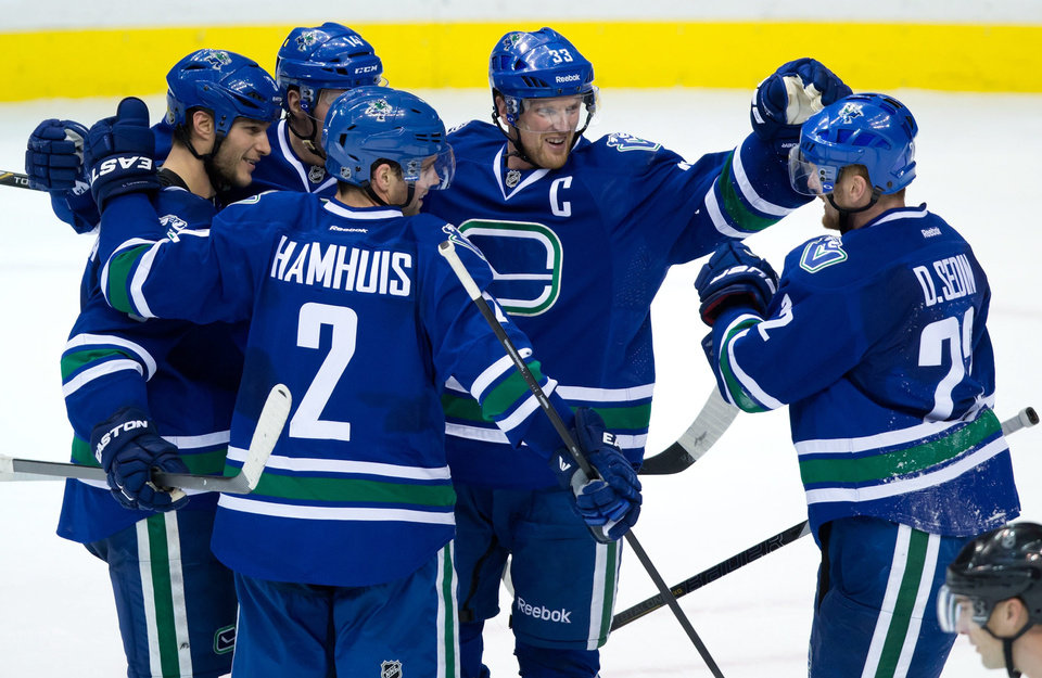 Vancouver Canucks' Kevin Bieksa, from left to right, Alex Burrows, Dan Hamhuis, Henrik Sedin, of Sweden, and Daniel Sedin, of Sweden, celebrate Bieksa's goal against the San Jose Sharks during second period NHL hockey action in Vancouver, British Columbia, on Thursday Nov. 14, 2013. (AP Photo/The Canadian Press, Darryl Dyck)