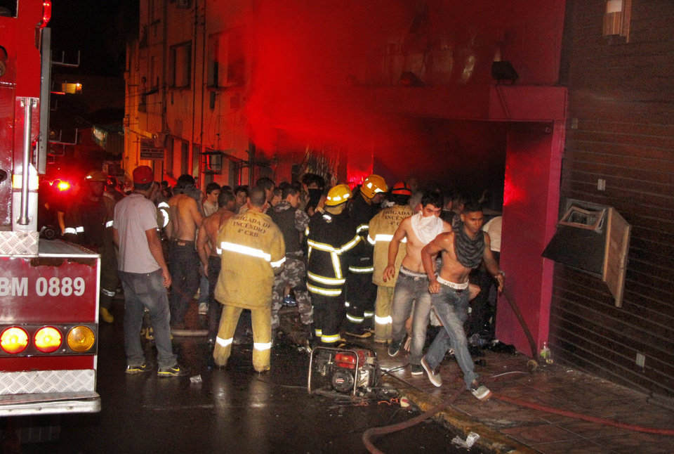 In this photo released by Agencia Brasil, people gather outside the Kiss nightclub as firefighters respond to a fire inside the club in Santa Maria, Brazil, Sunday, Jan. 27, 2013. A fast-moving fire roared through the crowded, windowless Kiss nightclub in this southern Brazilian city early Sunday, killing more than 230 people. Many of the victims were under 20 years old, including some minors. (AP Photo/Deivid Dutra, Agencia Brasil) ORG XMIT: XSI111