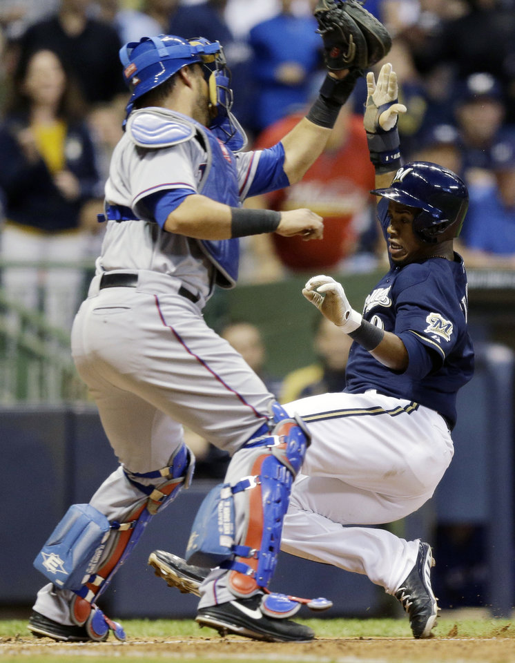 Photo - Texas Rangers catcher Geovany Soto tags out Milwaukee Brewers' Jean Segura at home during the third inning of a baseball game Wednesday, May 8, 2013, in Milwaukee. Segura tried to score from second on a hit by Aramis Ramirez. (AP Photo/Morry Gash)