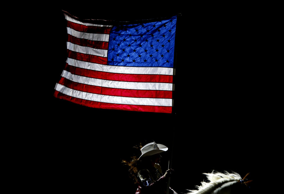 A rider carries an American flag before the International Finals Rodeo inside the State Fair Arena in Oklahoma City, Friday, Jan. 18, 2013. Photo by Bryan Terry, The Oklahoman