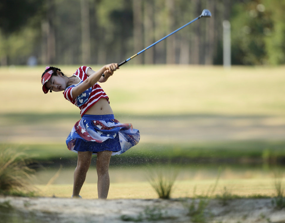 Photo - Lucy Li hits from a waste area on the 15th fairway during the first round of the U.S. Women's Open golf tournament in Pinehurst, N.C., Thursday, June 19, 2014. (AP Photo/Chuck Burton)