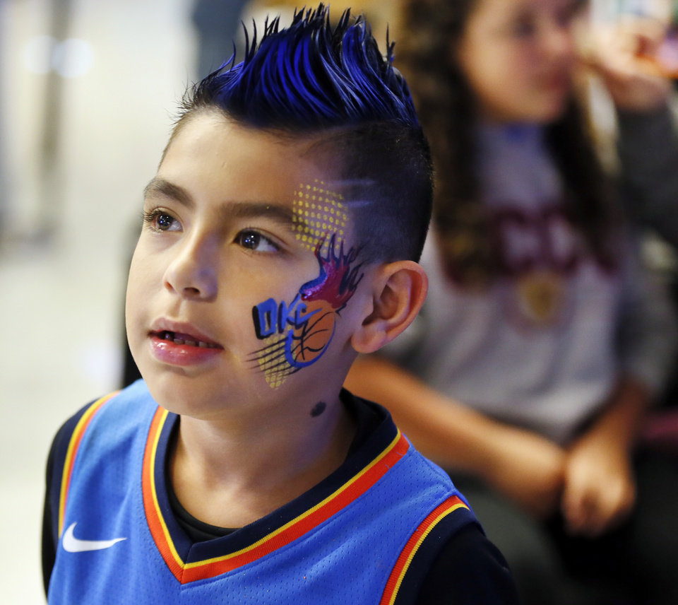 Photo - Thunder fan Louis Ortega, 7, stands up after having his face painted before an NBA basketball game between the Oklahoma City Thunder and the Washington Wizards at Chesapeake Energy Arena in Oklahoma City, Friday, Oct. 25, 2019. [Nate Billings/The Oklahoman]