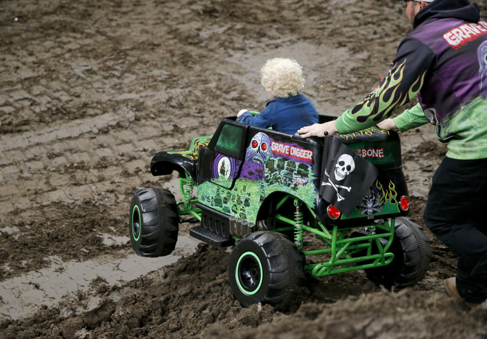 Photo - Monster Jam driver Grave Digger, Brandon Vinson, helps Ryker Ammons, 4, of Yukon, Okla., down a a hill on the the track at Chesapeake Energy Arena in Oklahoma City, Friday, Feb. 14, 2020.  [Sarah Phipps/The Oklahoman]