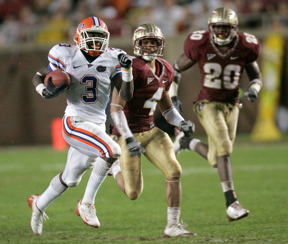 Photo - Florida running back Chris Rainey, left, runs away from Florida State cornerback Tony Carter, center, and Florida State safety Jamie Robinson, right,  during the third quarter of an NCAA college football game Saturday, Nov. 29, 2008, in Tallahassee, Fla.  Florida won 45-15.(AP Photo/Phil Coale) ORG XMIT: FLPC212
