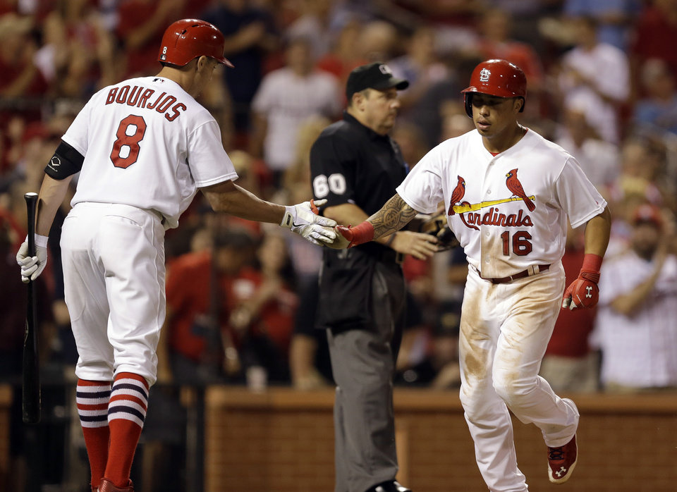 Photo - St. Louis Cardinals' Kolten Wong, right, is congratulated by teammate Peter Bourjos after hitting a solo home run during the seventh inning of a baseball game against the Pittsburgh Pirates Wednesday, July 9, 2014, in St. Louis. (AP Photo/Jeff Roberson)