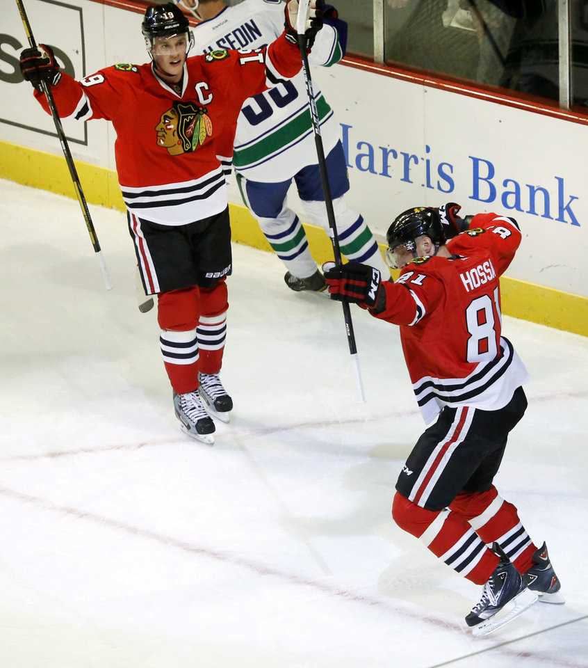 Photo - Chicago Blackhawks right wing Marian Hossa (81), from Slovakia, celebrates his second goal of the game with Jonathan Toews (19) during the second period of an NHL hockey game against the Vancouver Canucks Tuesday, Feb. 19, 2013 in Chicago. (AP Photo/Charles Rex Arbogast)