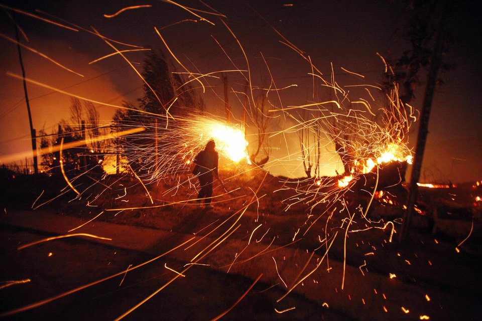 Photo - A person tries to extinguish flames as sparks fly during a forest fire in Valparaiso, Chile, early Sunday, April 13, 2014. Authorities say the fires have destroyed hundreds of homes, forced the evacuation of thousands and claimed the lives of at least seven people. (AP Photo/Luis Hidalgo)