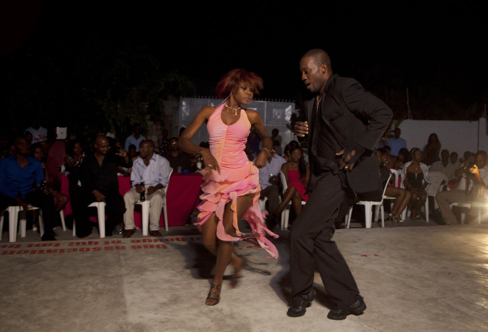Photo - In this Jan. 20, 2013 photo, professional dancer Georges Exantus, right, performs with Modeline Gene Arhan during a show in Port-au-Prince, Haiti. Exantus thought he'd never dance again. The earthquake three years ago in Haiti's capital flattened the apartment where he was living where he spent three days trapped under a heap of jagged rubble. After friends dug him out, doctors amputated his right leg just below the knee. Three years later, the 32-year-old professional dancer is back on the floor, spinning away as he does the salsa, cha-cha and samba. A prosthetic leg doesn't hold him back. (AP Photo/Dieu Nalio Chery)