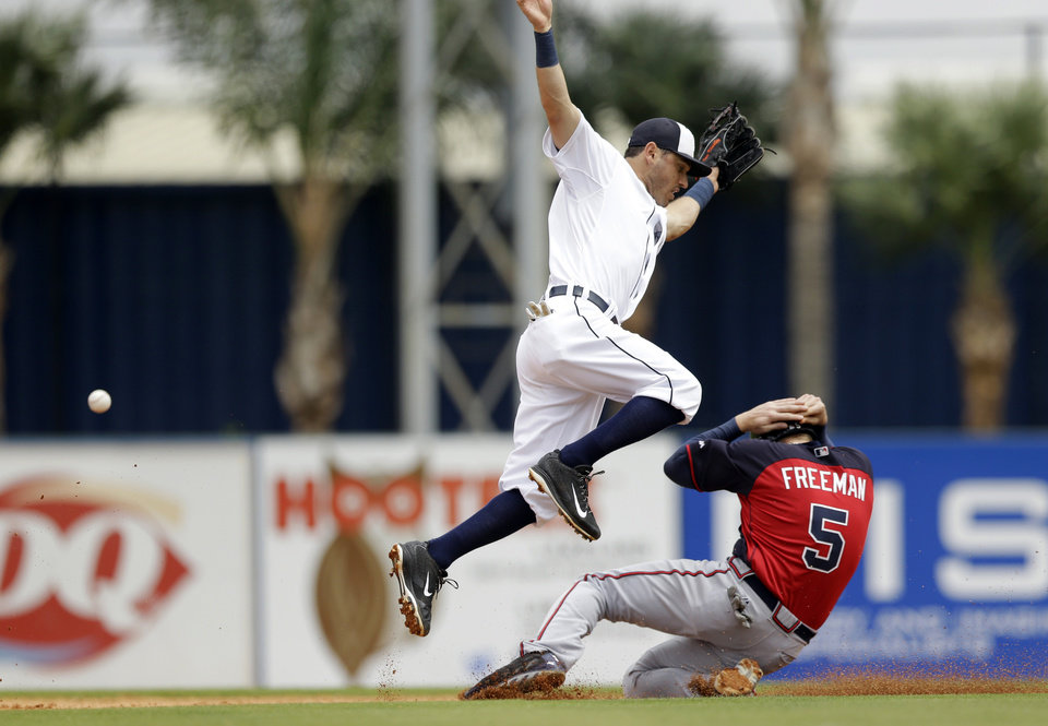 Photo - Detroit Tigers second baseman Ian Kinsler loses control of the ball as Atlanta Braves first baseman Freddie Freeman, right, slides under for a steal during the third inning of a spring exhibition baseball game in Lakeland, Fla., Tuesday, March 25, 2014. (AP Photo/Carlos Osorio)