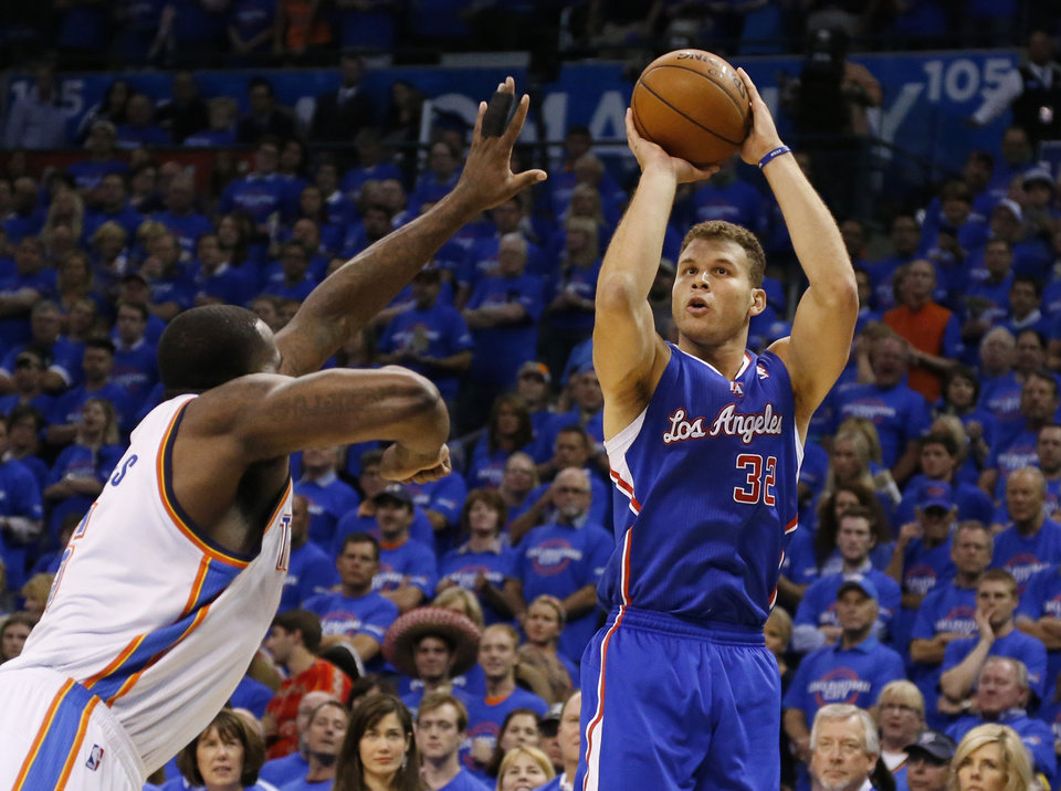 Photo - Los Angeles Clippers forward Blake Griffin,right, shoots over Oklahoma City Thunder center Kendrick Perkins, left, in the first quarter of Game 1 of the Western Conference semifinal NBA basketball playoff series in Oklahoma City, Monday, May 5, 2014. (AP Photo/Sue Ogrocki)