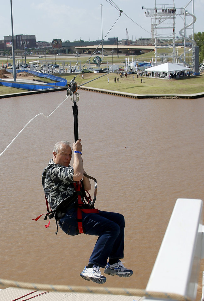 Photo - Barry Switzer lands on the south side of the Oklahoma River as he rides rides the new SandRidge Sky Zip in the Boathouse District in Oklahoma City, Thursday May, 22, 2014. Photo by Bryan Terry, The Oklahoman