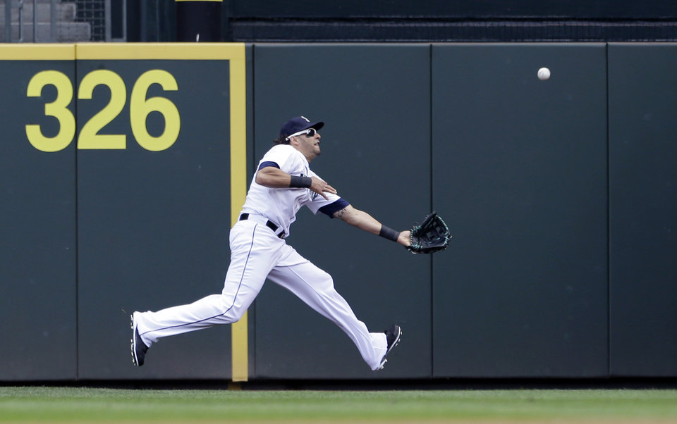 Photo - Seattle Mariners right fielder Michael Morse chases down a fly ball from Los Angeles Angels' Kole Calhoun into foul territory in the first inning of a baseball game, Sunday, Aug. 25, 2013, in Seattle. Morse made the catch. (AP Photo/Elaine Thompson)