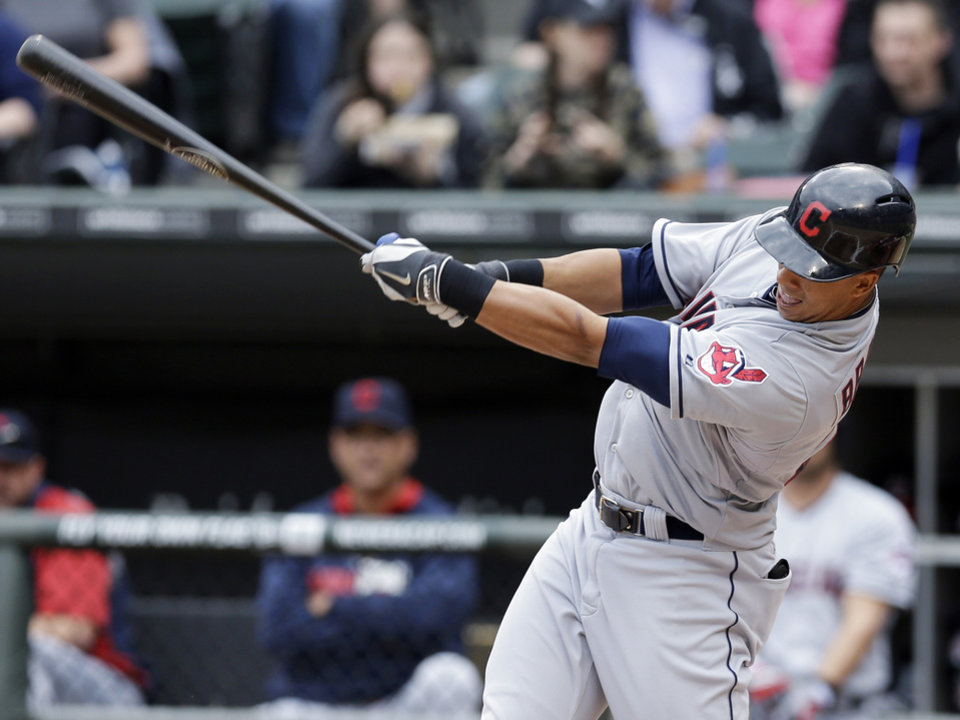 Photo - Cleveland Indians' Michael Brantley hits a two-run single against the Chicago White Sox during the first inning of a baseball game in Chicago on Saturday, April 12, 2014. (AP Photo/Nam Y. Huh)