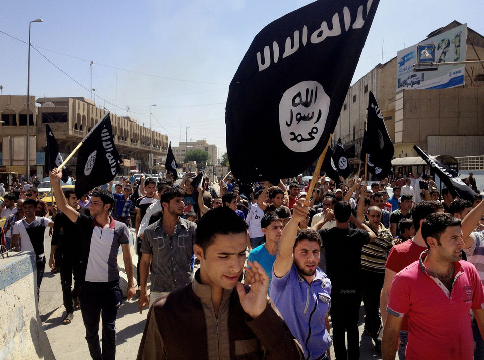 Photo - FILE - In this Monday, June 16, 2014 file photo, demonstrators chant slogans to support al-Qaida-inspired Islamic State of Iraq and the Levant as they carry al-Qaida flags in front of the provincial government headquarters in Mosul, 225 miles (360 kilometers) northwest of Baghdad, Iraq. The al-Qaida breakaway group that has seized much of northern Syria and huge tracks of neighboring Iraq formally declared the creation of an Islamic state on Sunday, June 29, in the territory under its control. (AP Photo, File)