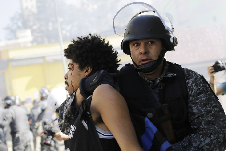 Photo - A protester is detained by police during a demonstration demanding better public services and protesting the money spent on the World Cup in Sao Paulo, Brazil, Thursday, June 12, 2014. Brazilian police clashed with anti-World Cup protesters trying to block part of the main highway leading to the stadium that hosts the opening match of the tournament. (AP Photo/Nelson Antoine)