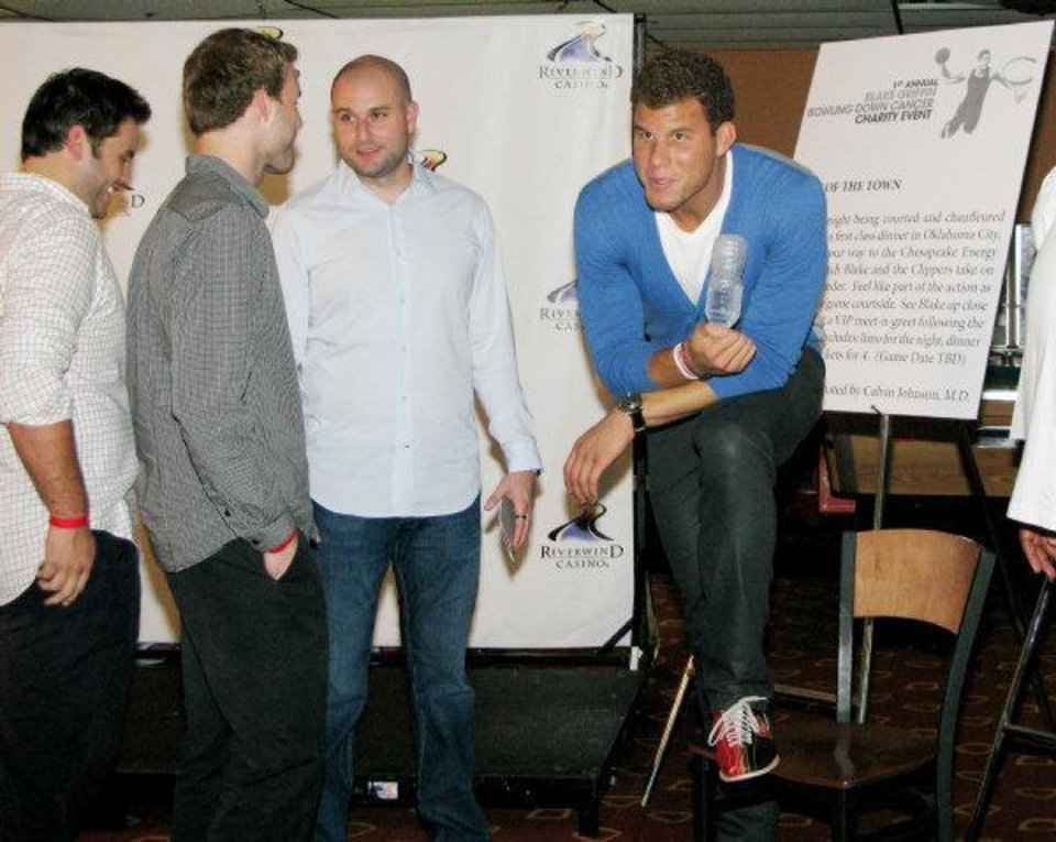 Blake Griffin, center, with bowling shoes on, takes a quick break before a live auction during his first Bowling Down Cancer Charity Event at the AMF Moore Lanes. PHOTO BY LILLIE-BETH BRINKMAN, THE OKLAHOMAN <strong></strong>