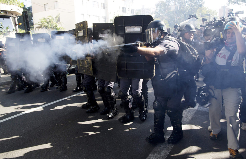 Photo - Police fire rubber bullets at protestors in Sao Paulo, Brazil, Thursday, June 12, 2014. Brazilian police have clashed with anti-World Cup protesters trying to block part of the main highway leading to the stadium that hosts the opening match of the tournament. (AP Photo/Rodrigo Abd)