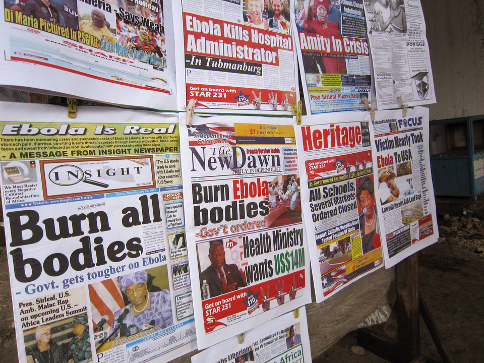 Photo - A close up of newspaper front pages focusing on the Ebola outbreak, including a newspaper, left,  reading 'Burn all bodies' in the city of Monrovia, Liberia, Thursday, July 31, 2014. The worst recorded Ebola outbreak in history surpassed 700 deaths in West Africa as the World Health Organization on Thursday announced dozens of new fatalities. (AP Photo/Jonathan Paye-Layleh)