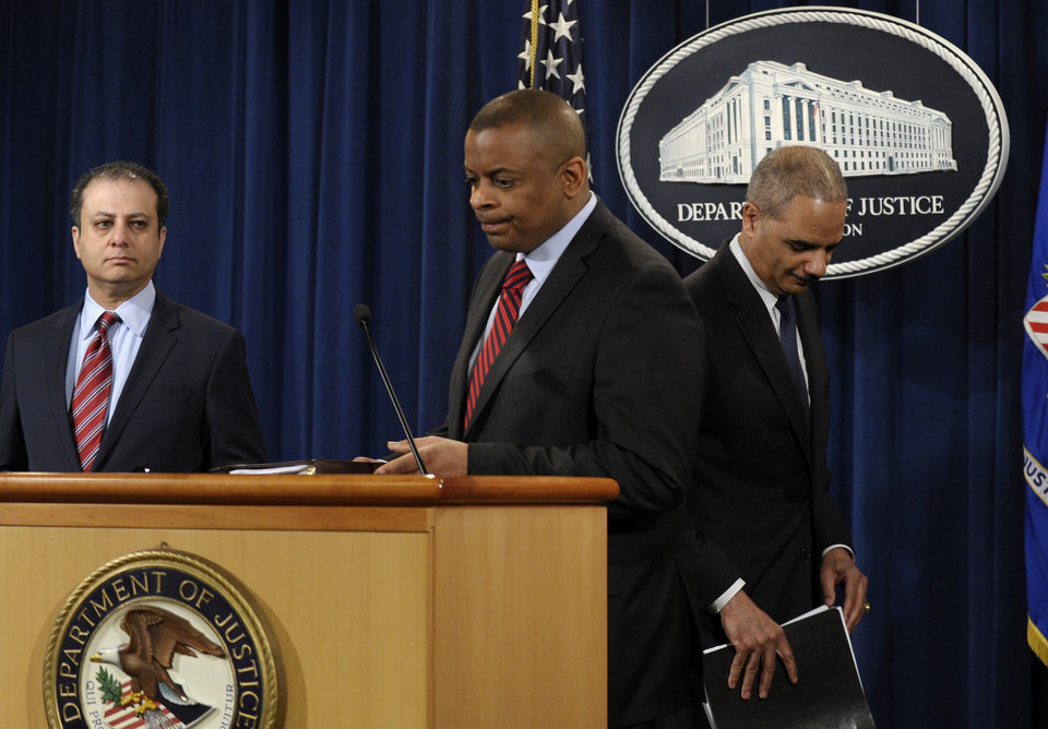 Photo - Attorney General Eric Holder, right, changes places with Transportation Secretary Anthony Foxx, center, during a news conference at the Justice Department in Washington, Wednesday, March 19, 2014, to announce a $1.2 billion settlement with Toyota over its disclosure of safety problems. U.S. Attorney for the Second District Preet Bharara is at left.  (AP Photo/Susan Walsh)