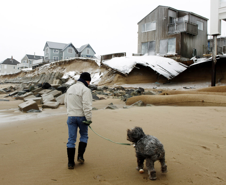 John March walks his dog Grommit past damaged houses along the beach in Plum Island in Newbury, Mass., Saturday, Feb. 9, 2013. (AP Photo/Winslow Townson)