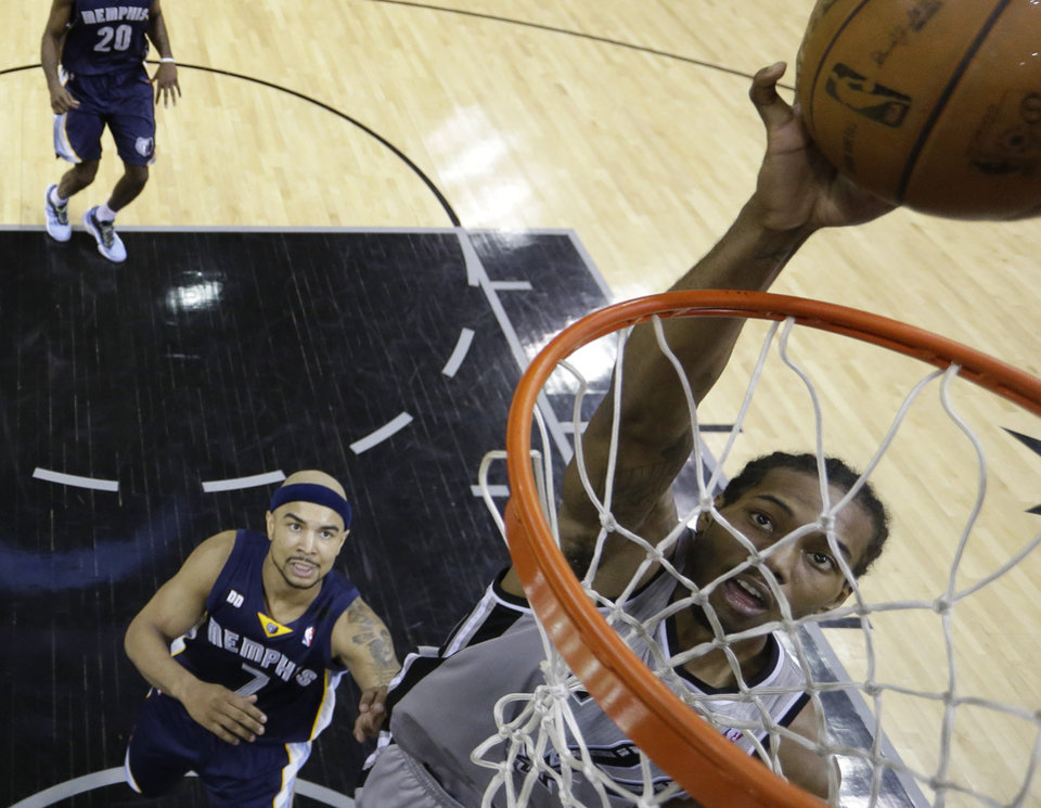 Photo - San Antonio Spurs' Kawhi Leonard, right, scores as Memphis Grizzlies' Jerryd Bayless (7) looks on during the second half in Game 1 of a Western Conference Finals NBA basketball playoff series, Sunday, May 19, 2013, in San Antonio. The Spurs won 105-83. (AP Photo/Eric Gay)