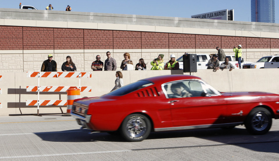 Spectators watch from the west bound lanes as a convoy of vehicles pass during grand opening ceremonies for the east bound lanes of the I-40 Crosstown in Oklahoma City Thursday, Jan. 5, 2012. Photo by Paul B. Southerland, The Oklahoman ORG XMIT: KOD