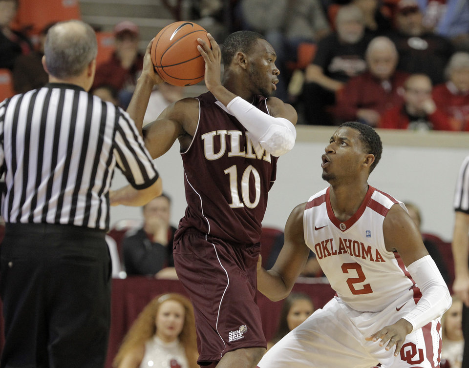 Photo - Oklahoma's Steven Pledger (2) guards Louisiana's Amos Olatayo (10) during a men's college basketball game between the University of Oklahoma and the University of Louisiana-Monroe at the Loyd Noble Center in Norman, Okla., Sunday, Nov. 11, 2012.  Photo by Garett Fisbeck, The Oklahoman