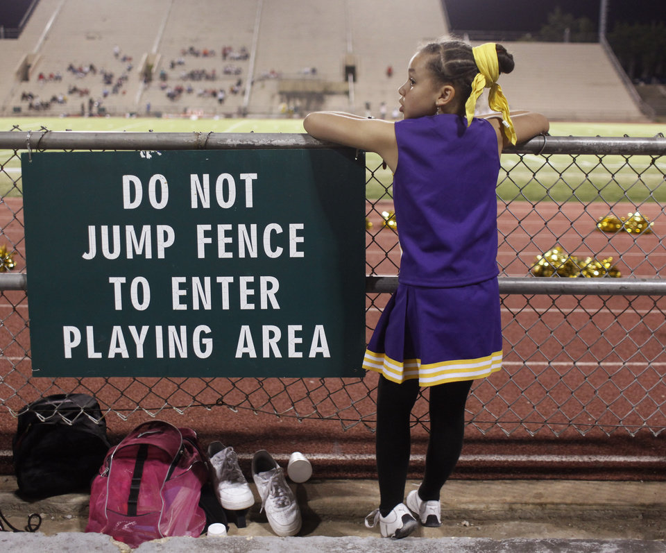 A young girl waits at the fence during halftime at the Northwest Classen vs. Western Heights high school football game at Taft Stadium Thursday, September 20, 2012. Photo by Doug Hoke, The Oklahoman