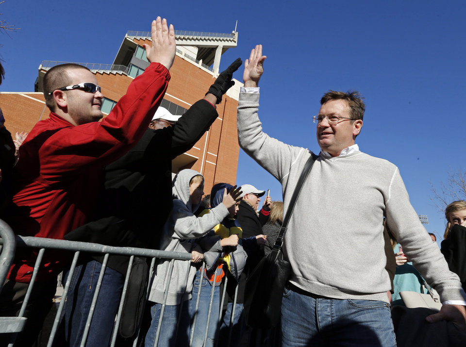 Oklahoma coach Bob Stoops is greeted by some of the fans gathered to welcome the football team as it returned from the Sugar Bowl NCAA college football game, Friday, Jan. 3, 2014 in Norman, Okla. Oklahoma defeated Alabama 45-31 on Thursday night. (AP Photo/The Oklahoman, Steve Sisney)