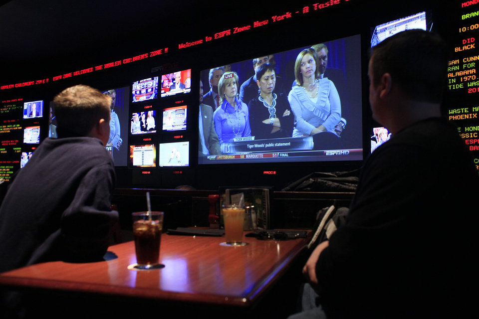 Photo - Patrons of the ESPN Zone in Times Square watch the Tiger Woods news conference, Friday, Feb. 19, 2010 in New York. Tiger Woods has apologized for having affairs and says he is unsure when he will return to competitive golf. (AP Photo/Mary Altaffer) ORG XMIT: NYMA102