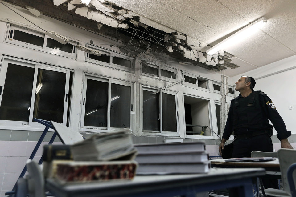 Photo -   An Israeli policeman examines the damage to a school classroom hit by a rocket fired by Palestinian militants from the Gaza Strip, at the southern Israeli city of Ashkelon, Monday, Nov. 19, 2012. Israeli aircraft struck crowded areas in the Gaza Strip and killed a senior militant with a missile strike on a media center Monday, driving up the Palestinian death toll to 96, as Israel broadened its targets in the 6-day-old offensive meant to quell Hamas rocket fire on Israel. (AP Photo/Tsafrir Abayov)