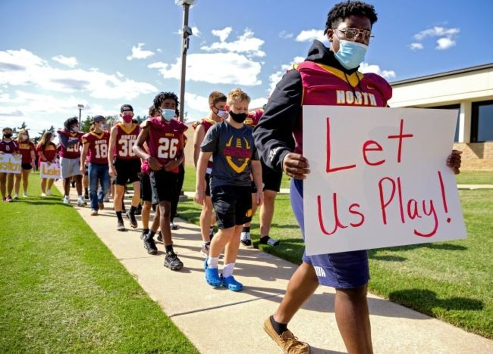 Photo -  Athletes from Putnam City North joined with athletes from Putnam City and Putnam City West on Monday to protest the district's decision to shut down sports due to COVID-19 at the Putnam City Schools administration building in Warr Acres.  [Chris Landsberger/The Oklahoman]