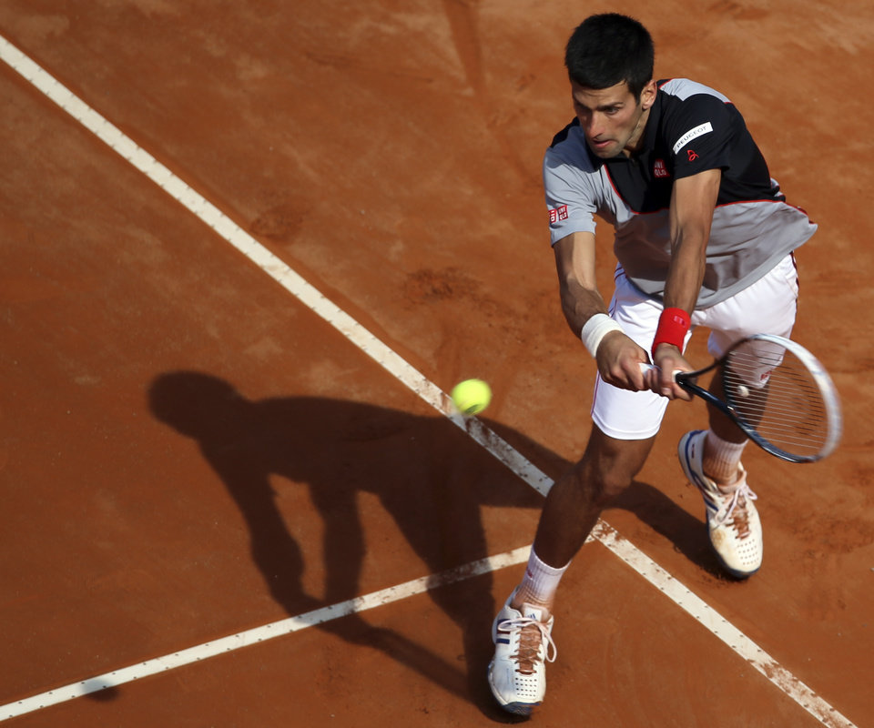 Photo - Serbia's Novak Djokovic returns a backhand during his semifinal match against Canada's Milos Raonic at the Italian open tennis tournament in Rome, Saturday, May 17, 2014. Djokovic won the match and advanced to the final. (AP Photo/Gregorio Borgia)