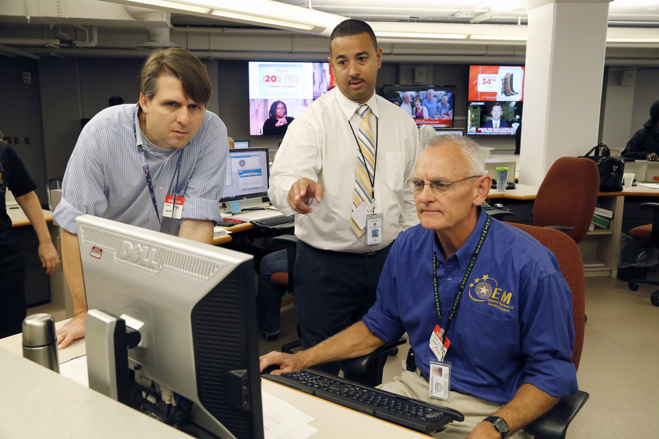 Photo -  Chance Morgan, left, Jared Coleman and Jerry Lojka work with state and local emergency managers in a statewide drill. [Paul Hellstern, The Oklahoman]
