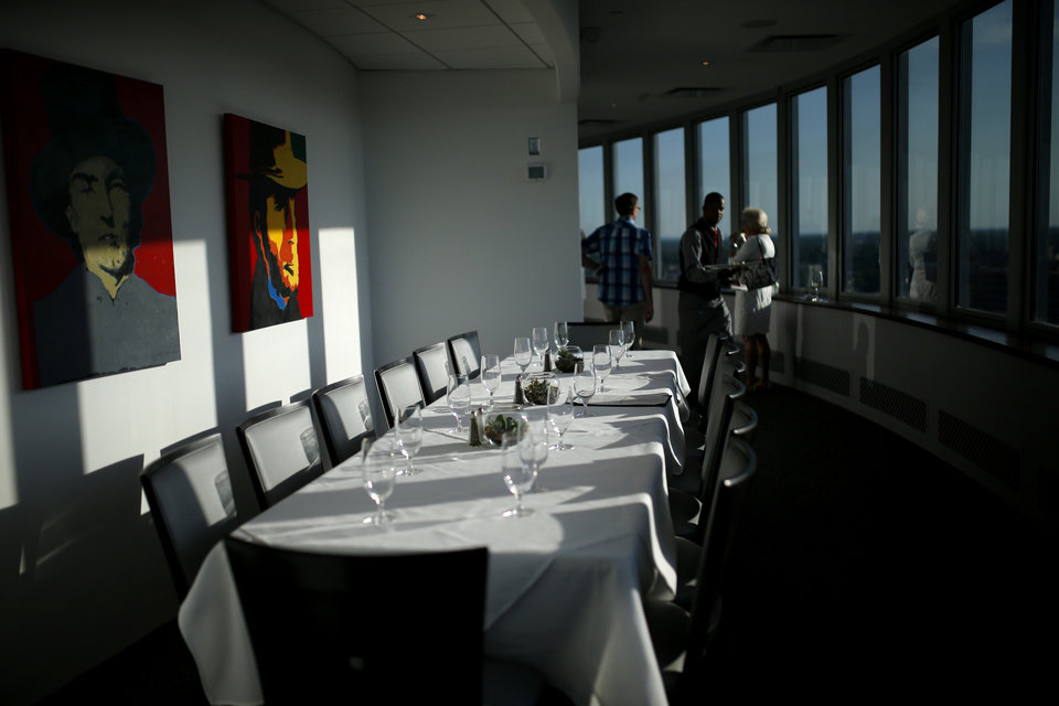 Photo -  A server walks past a table during a preview event at The George Prime Steakhouse atop the Founders Tower in Oklahoma City.