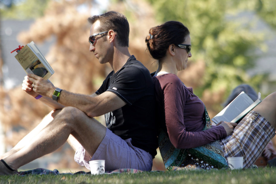 Scott and Kendra Plafker sit against each other reading during the Mesta Festa at Pearl Mesta Park in Oklahoma City Saturday, October 15, 2011. Photo by Doug Hoke, The Oklahoman