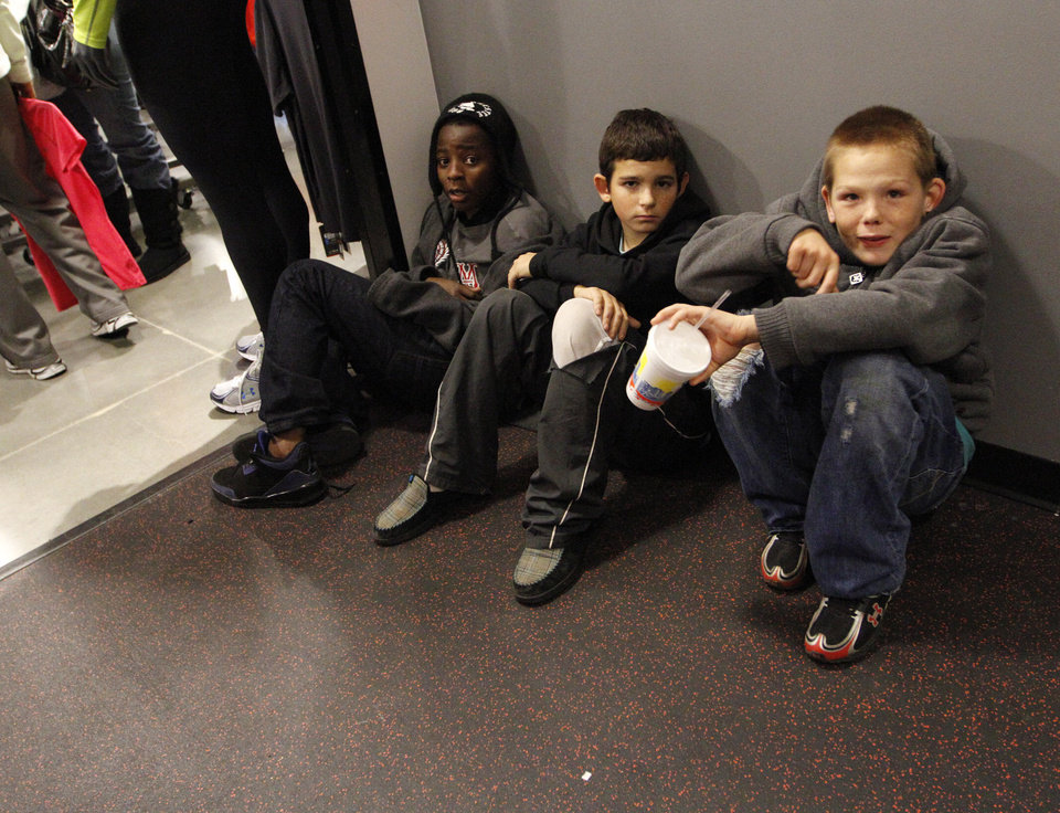 Photo - Christian Hoover, Blake Solmi, and Alex Cox wait outside of the dressing rooms at the Under Armour outlet during Black Friday at The Outlet Shoppes at Oklahoma City, Thursday, Nov. 24, 2011.  Photo by Garett Fisbeck, For The Oklahoman