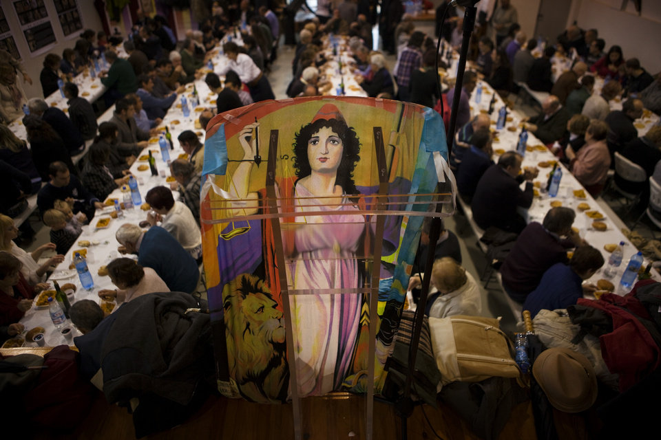 A poster of the Second Spanish Republic is seen as people eat their lunch during a ceremony following a burial of four residents, after their bodies were found in an unmarked dump dating from the country's civil war, in Torrellas, Zaragoza, Spain, Saturday, April 14, 2012. Pilar Perez, who presides over the town council of Torrellas, says the bodies were discovered and exhumed in October 2010. DNA analysis revealed they were those of former mayor Gregorio Torres and residents Luis Torres, Feliciano Lapuente and Marcelino Navarro. All four had been driven out of town and shot by forces loyal to Gen. Francisco Franco in 1936 after the beginning of the war, which lasted until 1939. Relatives and around 200 residents attended a ceremony at the town hall on Saturday before a formal burial in the town's cemetery. (AP Photo/Emilio Morenatti)