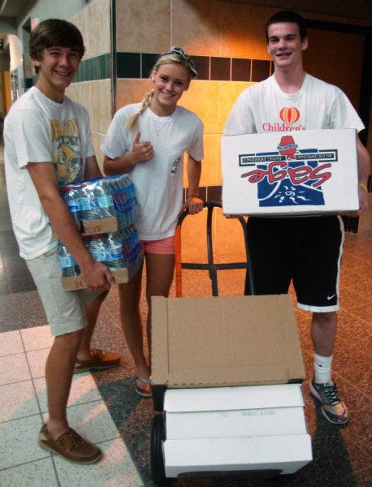 Edmond Santa Fe High School Student Council members, from left, Storm Rund, Julie Stockton and Kaleb Kadavy help move boxes of food and water they collected for tornado victims. PHOTO PROVIDED BY EARL KIRKPATRICK, NEWSOK.COM CONTRIBUTOR  <strong></strong>