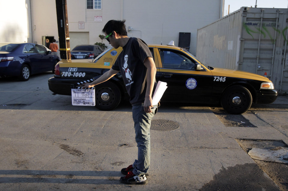 Photo -   In this Dec. 16, 2011 photo, crew member Arthur Hong holds a clapboard while filming holiday movie trailers at the Maker Studios in Culver City, Calif. The $100 million investment by YouTube in 96 new channels starting in October has sparked a flurry of activity in Hollywood's independent producer community. At companies like Maker Studios, which received money for three new channels, the funds have turbo-charged an already teeming operation. (AP Photo/Jae C. Hong)