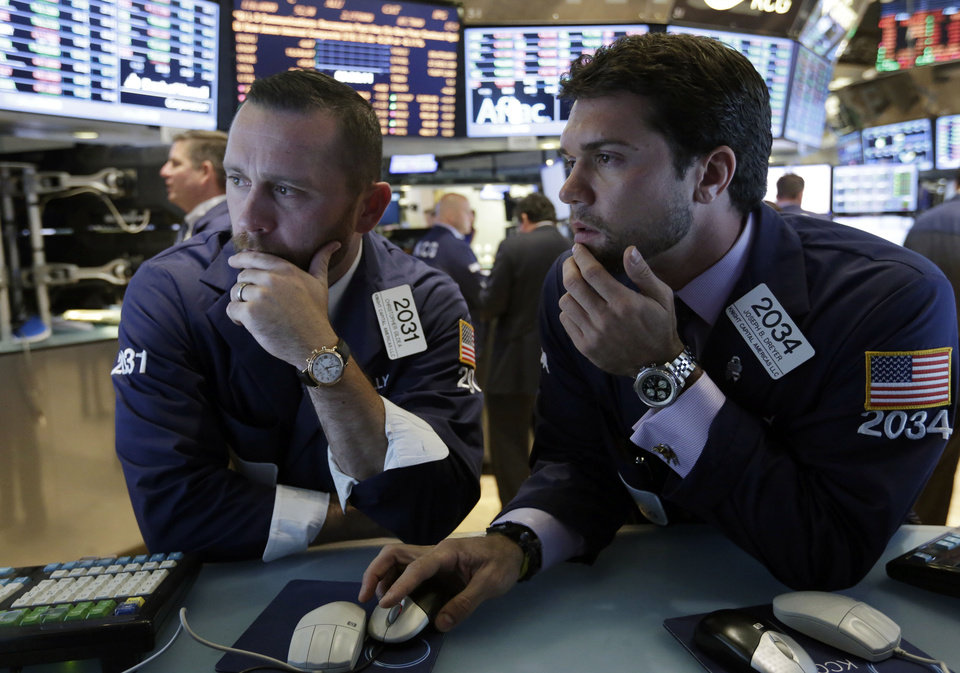 Photo - Specialists Christopher Gildea, left, and Joseph Dreyer, confer at their posts on the floor of the New York Stock Exchange Monday, July 22, 2013. The stock market edged higher as a big week of earnings kicked off Monday, with mixed results from a handful of large U.S. companies. (AP Photo/Richard Drew)