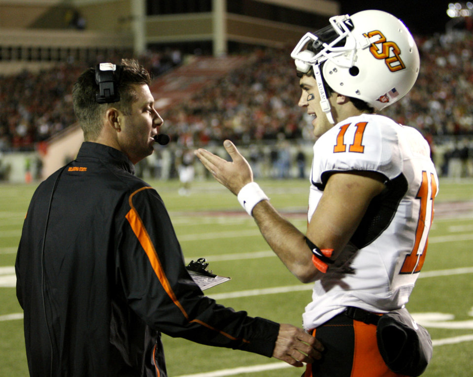 Photo - Head coach Mike Gundy talks with quarterback Zac Robinson during the second half of the college football game between the Oklahoma State University Cowboys (OSU) and the Texas Tech Red Raiders at Jones AT&T Stadium on Saturday, Nov. 8, 2008, in Lubbock, Tex.  Texas Tech won 56-20.  By Steve Sisney/The Oklahoman KOD
