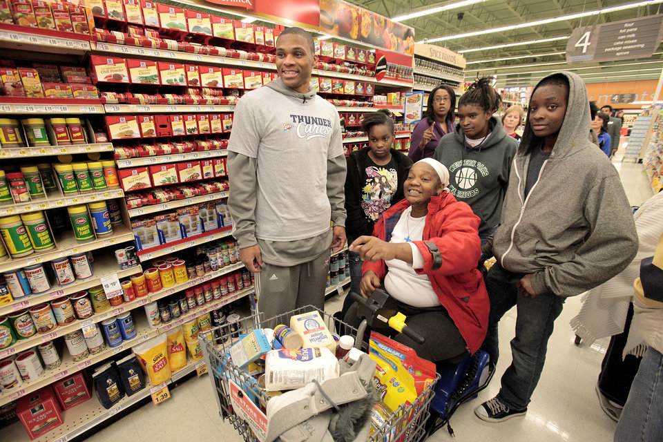OKAHOMA CITY THUNDER NBA BASKETBALL TEAM / GROCERY STORE / SHOPPING / ERACA RAID / MATTHEW RAID: The Thunder's Russell Westbrook shops with  Angela Raid, center, and her children Melissa Raid, 12, Eraca,14, and Matthew, 15, in a Homeland at Britton and May, Thursday, December 22 , 2011.  Photo by David McDaniel, The Oklahoman  ORG XMIT: KOD
