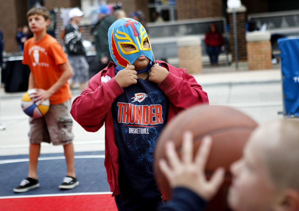 Photo - Luke Gosvener, 7, of Moore adjusts his mask before the NBA basketball game between the Denver Nuggets and the Oklahoma City Thunder in the first round of the NBA playoffs at the Oklahoma City Arena, Wednesday, April 27, 2011. Photo by Bryan Terry, The Oklahoman