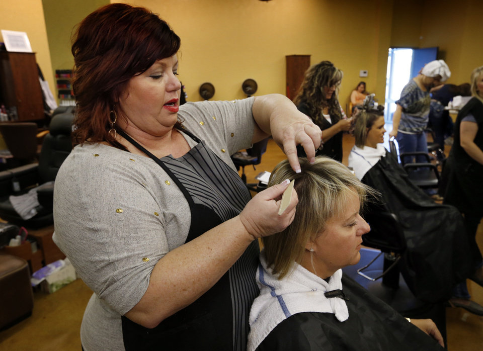 Sharese Tate, owner of Trenz Salon, works on her client, Staci Aduddell, at the shop's temporary location in the Malibu Shopping Center. <strong>Steve Sisney - THE OKLAHOMAN</strong>