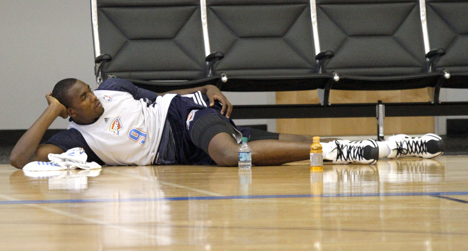 Photo - Oklahoma City's Serge Ibaka stretches following the Thunder's practice in Oklahoma City, Sunday, Dec. 11, 2011. Photo by Sarah Phipps, The Oklahoman