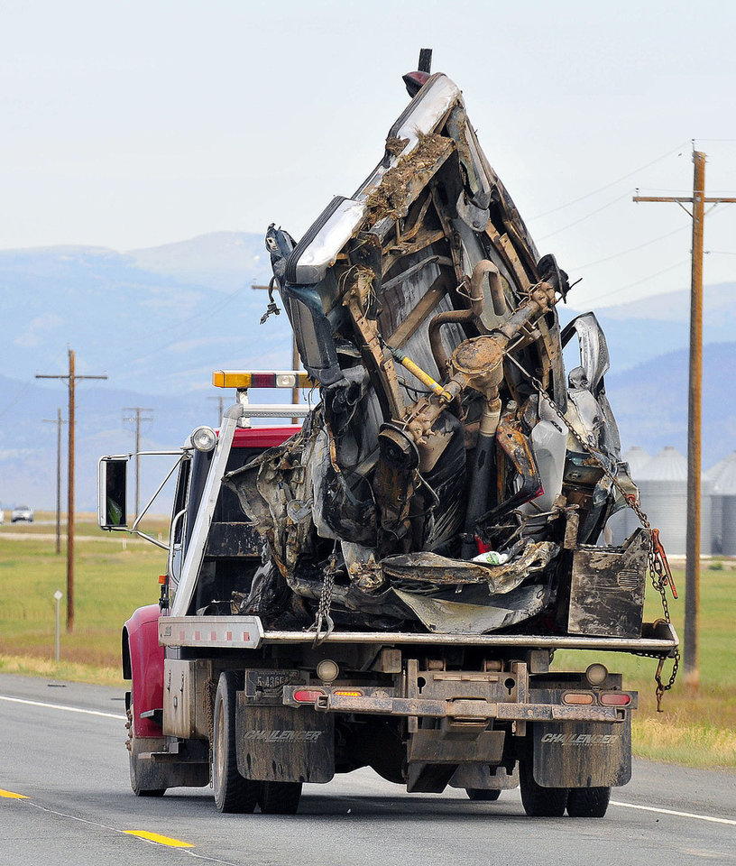 Photo - The wreckage of a pickup truck involved in a fatal accident is taken away from the scene Friday, June 20, 2014 near Helena, Mont. A fire engine and a pickup truck collided on the highway in southwestern Montana, causing an explosion and fire that killed six people, including a fire chief and three Helena children. There were no survivors. A Three Forks fire engine heading east on U.S. Highway 12 collided with a westbound pickup Thursday night, about 10 miles east of Helena, forcing both vehicles into the ditch, Jefferson County Sheriff's Deputy Bob Gleich said.  (AP Photo/The Independent Record, Eliza Wiley)