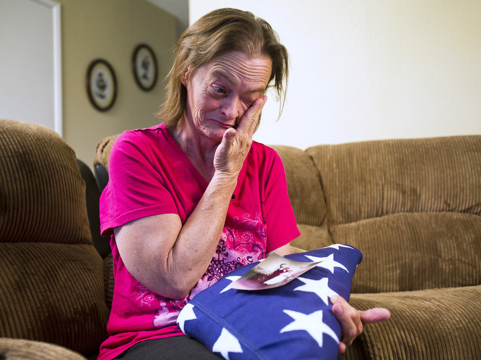Photo - Vicky Olson wipes away a tear May 9, 2014 while talking about her husband, Michael Olson, a Marine veteran who died at home in their garage in March at age 45.  Vicky holds their wedding photograph , as well as a United States flag given to her at a memorial service for Michael. (AP Photo/The Arizona Republic, Tom Tingle)
