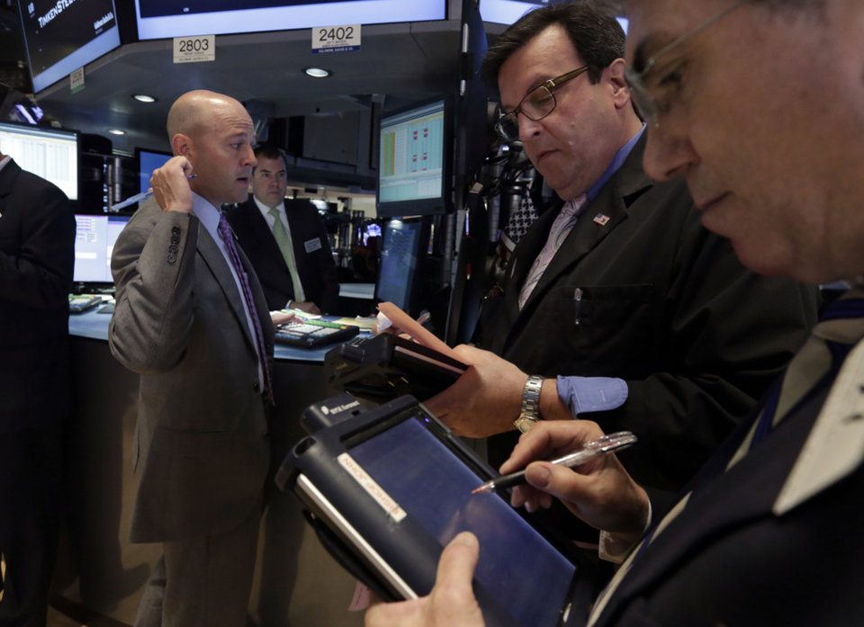 Photo - Traders Benedict Willis, center, and John Bishop, right, work with specialist Jay Woods on the floor of the New York Stock Exchange Tuesday, July 1, 2014. The stock market rose in early trading after a report showed that manufacturing in the US and China expanded in June, boosting the outlook for global growth. (AP Photo/Richard Drew)