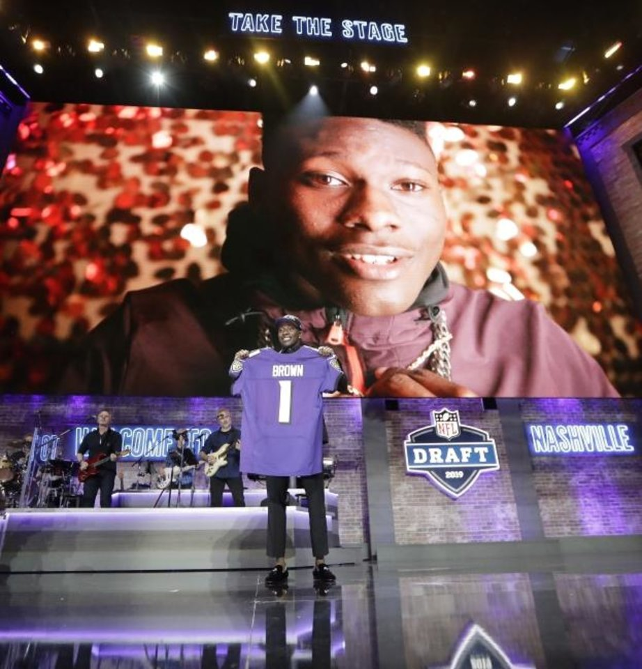 Photo -  Oklahoma wide receiver Marquise Brown poses with his new jersey after the Baltimore Ravens Brown selected in the first round at the NFL football draft, Thursday, April 25, 2019, in Nashville, Tenn.(AP Photo/Mark Humphrey)